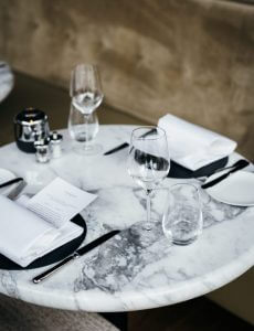 tavolo marmo apparecchiato con piatti neri