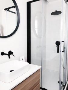 bagno moderno bianco rubinetti neri e legno